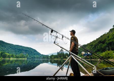 Le avventure di pesca, la pesca alla carpa. Il pescatore sulla riva di un lago in una mattinata con cielo scuro Foto Stock