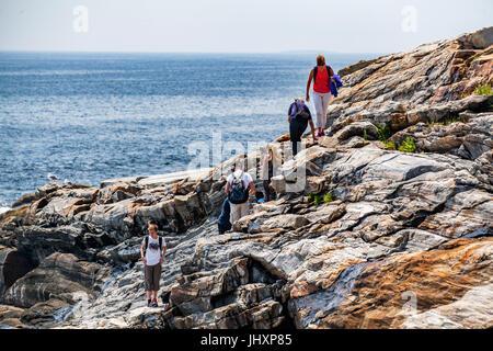 Una famiglia in vacanza si arrampica su rocce lungo la costa della Baia di Pemaquid a Bristol, Maine, Stati Uniti Foto Stock