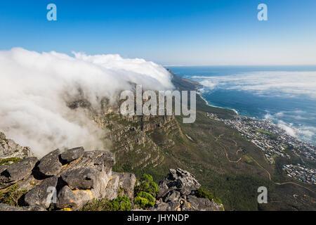 Table Mountain ricoperto di una tovaglia di nubi orografiche, Camps Bay al di sotto di coperte di bassa cloud, Cape Foto Stock