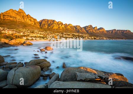 Tramonto a Camps Bay con Table Mountain sulla sinistra e i dodici Apostoli a destra, Western Cape, Sud Africa Foto Stock
