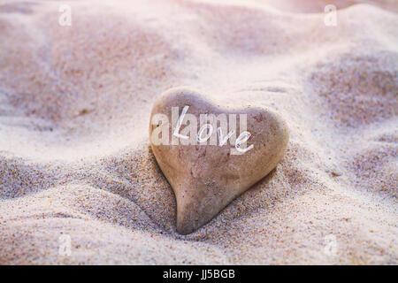 Il concetto di amore, cuore sulla sabbia, bello il giorno di san valentino card, colori vintage Foto Stock