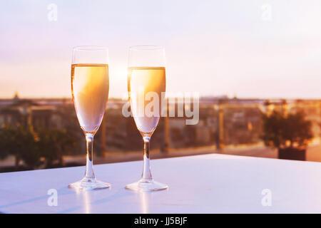 Due bicchieri di champagne al ristorante sul tetto con vista dello skyline della città, lusso cena romantica per Foto Stock