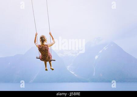 Concetto di felicità, felice bambine sullo swing sul bellissimo paesaggio di montagna sullo sfondo Foto Stock