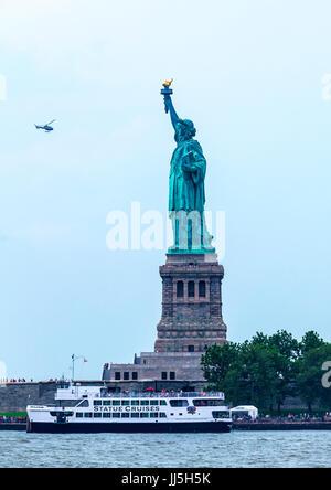 Statua della Libertà con un elicottero che vola i turisti a vedere il famoso dono del popolo della Francia Foto Stock