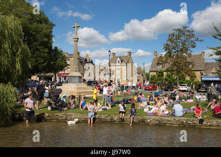 La folla di persone accanto al Fiume Windrush su agosto weekend festivo, Bourton-on-the-acqua, Cotswolds, Gloucestershire, Foto Stock