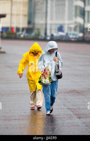Un paio in pioggia meteo abbigliamento sfidando la pioggia torrenziale sul lungomare della famosa città costiera Foto Stock