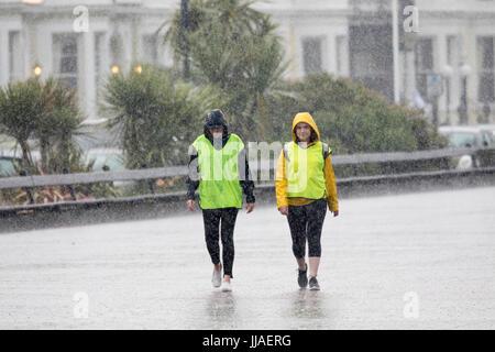 Una coppia di donne in pioggia meteo abbigliamento sfidando la pioggia torrenziale sul lungomare della famosa città Foto Stock