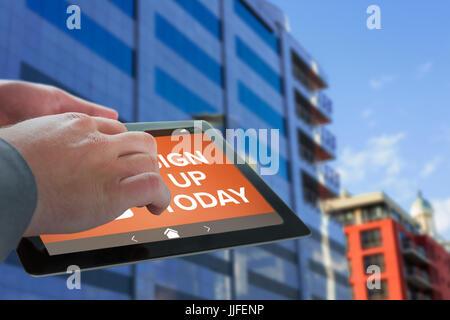 Imprenditore toccando lo schermo della compressa contro la riflessione sul palazzo di vetro Foto Stock
