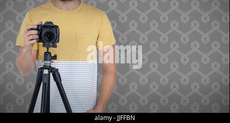 La sezione centrale del fotografo maschio fotografando attraverso la telecamera su un cavalletto sullo sfondo Foto Stock