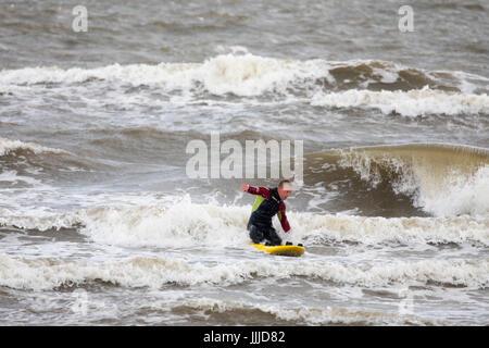 Un maschio RNLI lifeguard arrivando alla riva su una scheda di soccorso avente le pratiche in mare mosso nella località Foto Stock