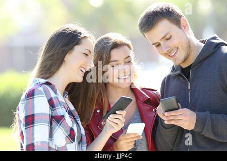 Tre felice teen amici di condivisione smart phone contenuto all'aperto Foto Stock