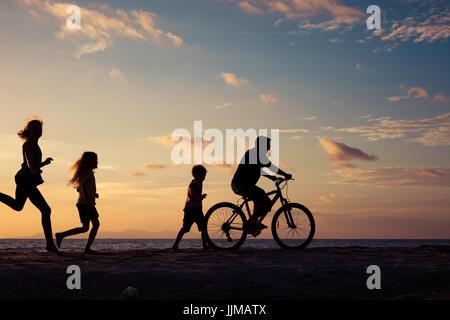 Padre e figli giocando sulla spiaggia al tramonto. Concetto di famiglia amichevole. Foto Stock