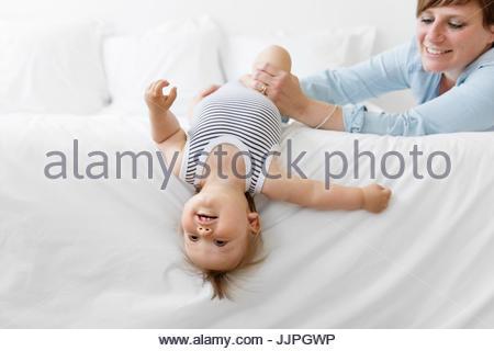 Donna sorridente con breve marrone capelli giocando con un bimbo che indossa un onesie striato, sdraiato sul letto Foto Stock