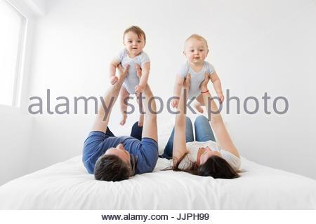 L uomo e la donna affiancati sulle loro spalle su un letto, ogni azienda aloft baby boy. Foto Stock