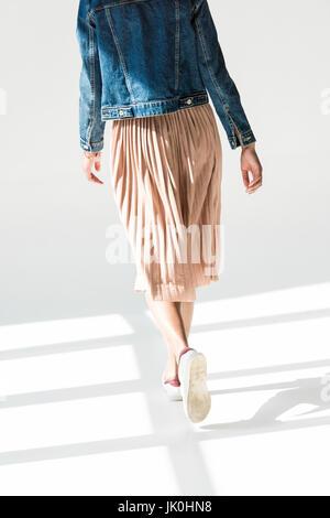 Vista posteriore, bassa angolazione della donna in beige gonna e giacca denim camminando in bianco studio Foto Stock
