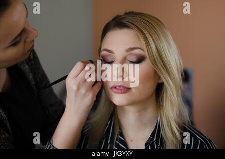 Giovane bella donna avente il suo make up fatto da un make up artist Foto Stock