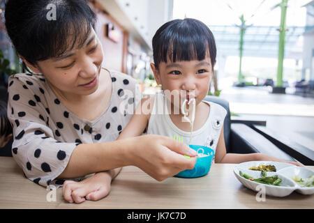 Asian madre cinese e la figlia di mangiare carne di manzo tagliatelle in outdoor cafe Foto Stock