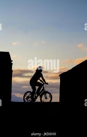 Silhouette di una ragazza in bicicletta Foto Stock
