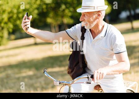 Uomo gioioso prendendo foto sul telefono Foto Stock