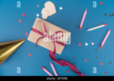 Vista superiore della scatola regalo di compleanno, hat e candele isolato sul blu, festa di compleanno di concetto