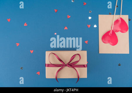 Vista superiore della confezione regalo a forma di cuore e coriandoli busta isolato sul blu, festa di compleanno di concetto
