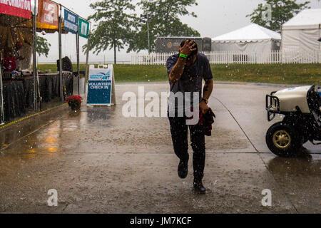 In esecuzione dalla pioggia con la sua mano sulla sua testa. Foto Stock