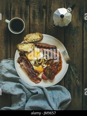 Prima colazione inglese tradizionale con uova fritte, salsicce, funghi e pancetta