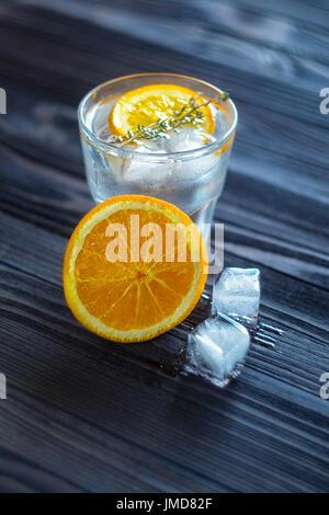 Un drink rinfrescante con Orange, cubetti di ghiaccio e rosmarino in un vetro su una tavola di legno scuro. Ancora Foto Stock