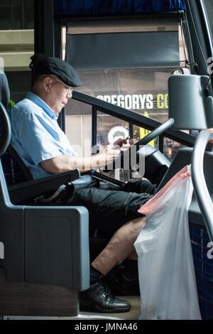 I vecchi Asian bus driver cercando sul suo telefono cellulare mentre prendendo una pausa sulla strada di New York Foto Stock