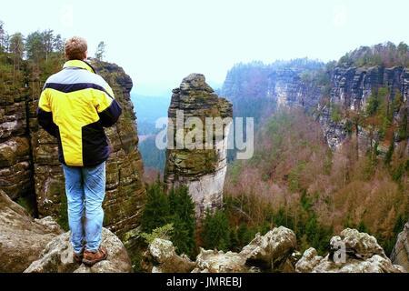 Alta turista escursionista uomo sulla roccia a picco nelle montagne  rocciose Foto Stock 7e558c9e443