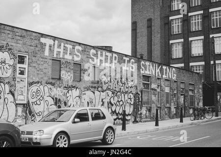 Street a Hackney Wick, East London, con graffiti sulla parete a leggere 'questa nave sta affondando'. Foto Stock
