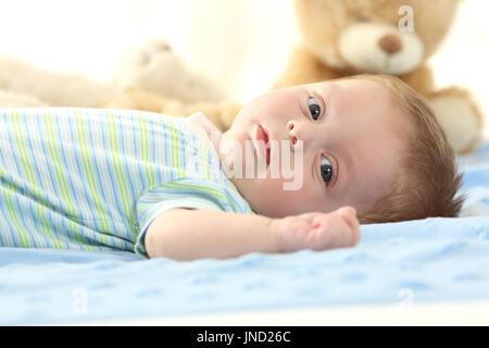 Ritratto di un bambino sdraiato su un letto e guardando a voi Foto Stock
