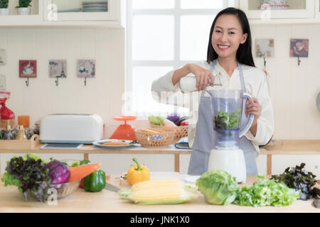 Frullato di vegetali. Donna asiatica rendendo frullati verde con blender home in cucina. Sana mangia crudo concetto Foto Stock