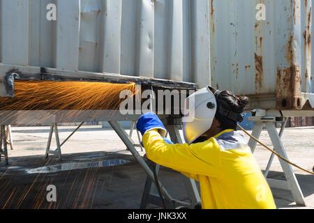 L'industria lavoratore con maschera protettiva in acciaio di saldatura per la riparazione di strutture di contenitore Foto Stock
