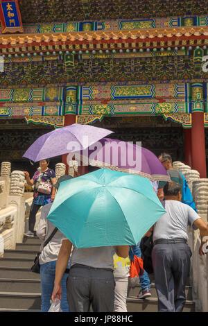 I turisti azienda ombra colorati ombrelloni avvicinando la sala della suprema armonia nella Città Proibita di Pechino, Foto Stock