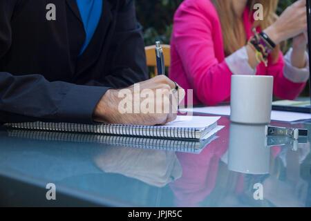 Il giovane imprenditore iscritto uno schema su un foglio bianco di un notebook sulla terrazza. Foto Stock