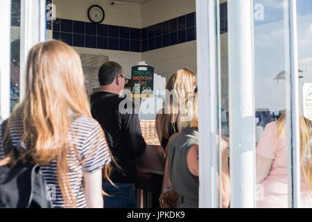 I clienti in attesa all'interno di un pesce e chip shop in Margate, Kent. Foto Stock