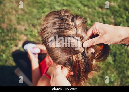 Giovane donna rendendo trecce di capelli della bambina sul giardino in campagna. Foto Stock