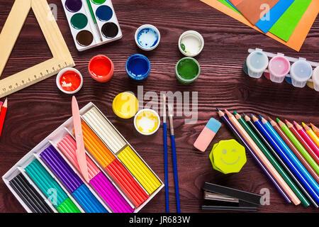 Forniture scolastiche su uno sfondo rosso, vernici e spazzole Foto Stock