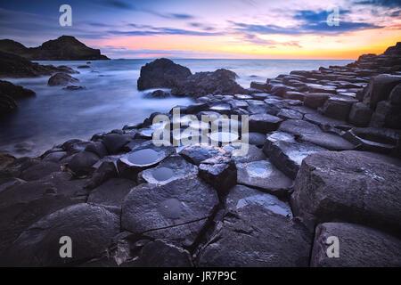 Tramonto su rocce basaltiche che formazione Giant's Causeway, Porto Ganny Bay e grande Stookan, County Antrim, Irlanda del Nord, Regno Unito