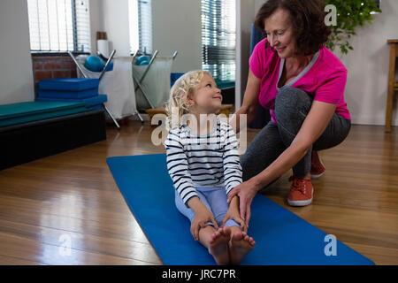Fisioterapista femminile aiutando ragazza paziente di eseguire esercizi di allungamento sul tappeto di esercizio Foto Stock