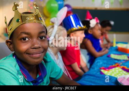 Ritratto di ragazzo sorridente indossando la corona con amici in background durante il party Foto Stock