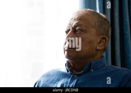 Close up di sad senior l uomo che guarda lontano mentre è seduto per finestra Foto Stock