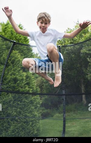 Mid Air Shot del ragazzo sul trampolino in giardino Foto Stock
