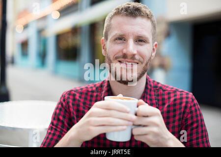 Ritratto di giovane uomo bere il caffè in Outdoor Cafe tabella Foto Stock