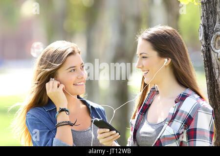 Due happy amici di condivisione on line di musica con auricolari all'aperto in un parco Foto Stock