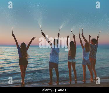 Sorridenti amici in spiaggia con spumante candele Foto Stock