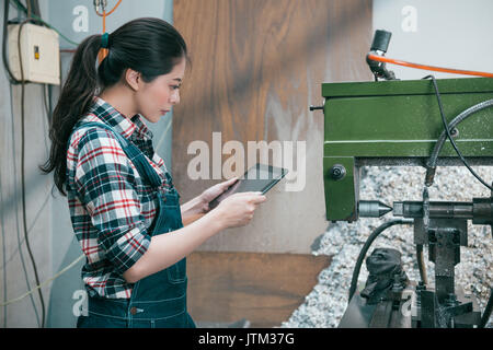 Bellezza elegante fabbrica di fresatura donna lavoratrice in piedi di fronte a lavorazioni industriali con tavoletta Foto Stock
