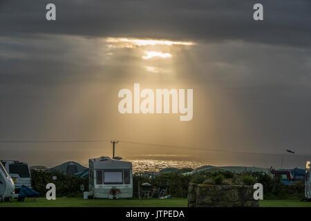 Raggi di sole rottura attraverso il cloud e illuminazione fino al mare accanto a un campeggio in Sennen (vicino al Lands End), Penzance, Corwall, Inghilterra, Regno Unito. Foto Stock