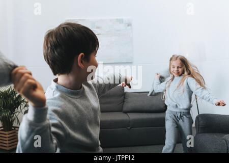 Piccolo Ragazzo e ragazza che gioca cuscino lotta in casa Foto Stock